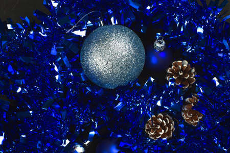 fir cones and blue and silvery New Year balls on a black background Reklamní fotografie - 92299790