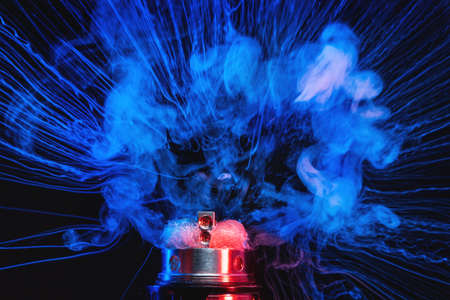 Electronic Cigarette vape explosion. Dark background.