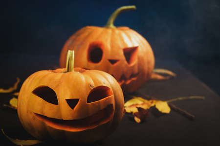 Halloween pumpkin lantern with dry leaves on black background Stock Photo