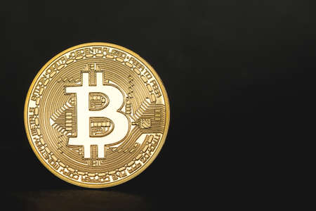 coin bitcoin on a black background stands on the edge