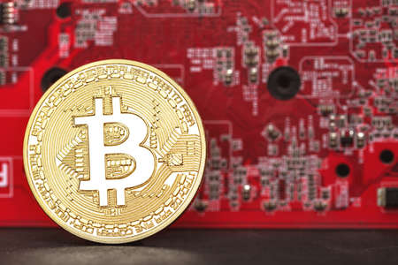 coin bitcoin against the background of the motherboard on the table