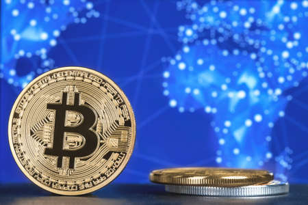 coin bitcoin against the background of the world map on the table   Reklamní fotografie