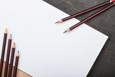 lot of colored pencils and drawing paper on a dark wooden background