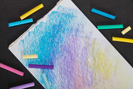 many colored crayons pastels and colored picture on a dark background Reklamní fotografie