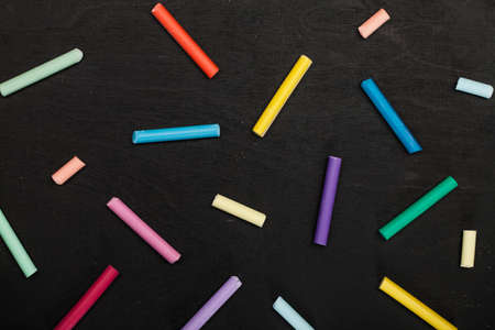 many colored crayons pastels on a dark background. pattern