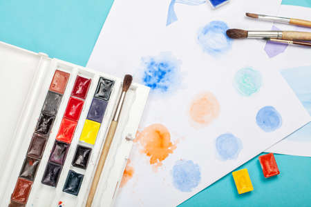 Brushes, paints and drawings on paper on a bright blue background