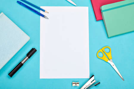 pens, scissors, notebooks and a white sheet of paper on a bright blue background. office tools  Reklamní fotografie