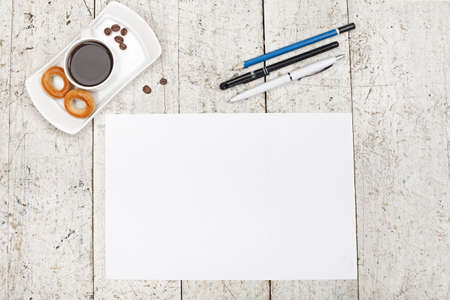 pens, pencils, white sheet of paper and coffee on a light wooden background  Reklamní fotografie