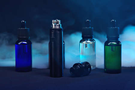 jars of liquids for vape in multi-colored smoke. dark background