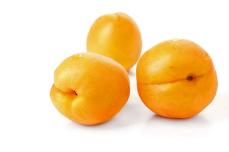 ripe juicy yellow apricots on a white table on a white background