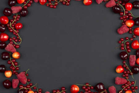 frame of ripe red currant berries cherries and raspberries on a black background