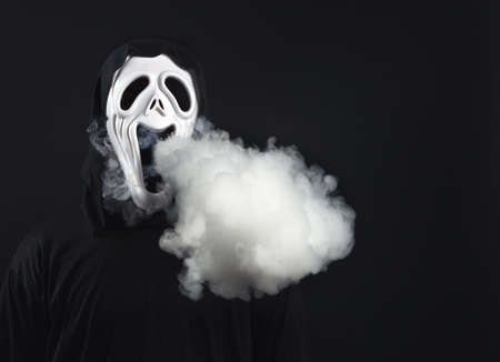 man in a terrible mask and black cloak cloud of vapor