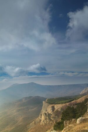 View on Crimean mountain and valley at horizont with clouds. rock in front of.  photo