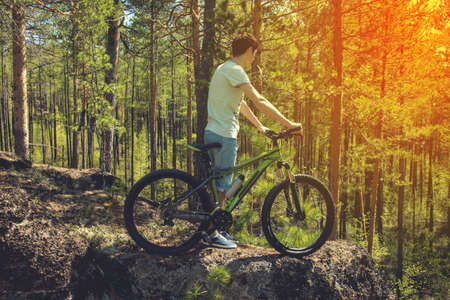 mountin: mountin biker with bike on the rocks. Successful happy rider on rocks holding bicycle. Sport, adventure, motivation and inspiration. Stock Photo