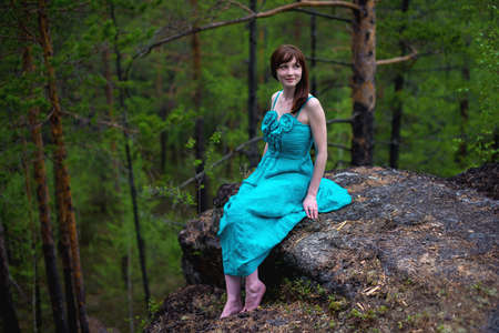 A beautiful young lady in elegant dress, enjoy the nature sitting in the woods on the rocks