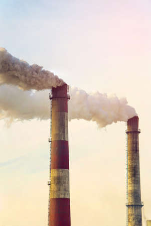 Smoking pipes of thermal power plant emitting carbon dioxide into the atmosphere at sunset, concept environment