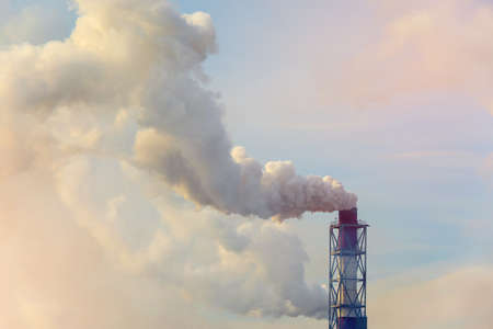 emitting: Smoking pipes of thermal power plant emitting carbon dioxide into the atmosphere at sunset, concept environment