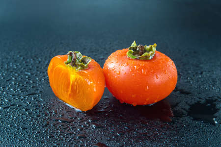 ripe persimmons with water drops on black background