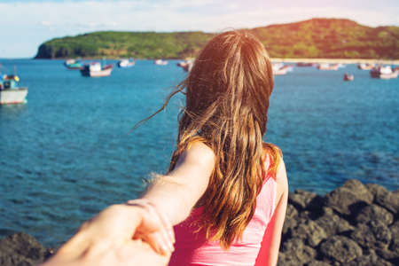 Woman with beautiful hair discovering jungle holding boyfriends hand. Follow me. Follow me. Travel concept.