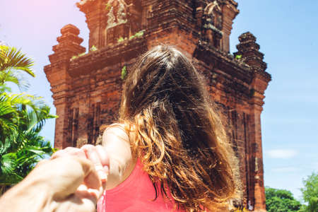 Woman with beautiful hair discovering an ancient temple holding boyfriends hand. Follow me. Follow me. Travel concept. Stock Photo