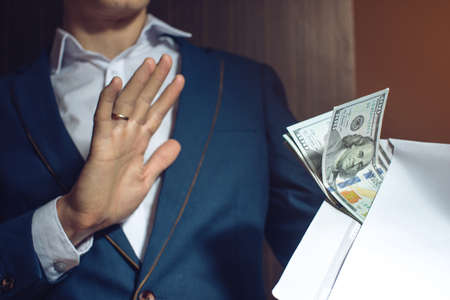 bribery: man businessman in suit refuses to take the bribe by showing that he was not corrupt. the concept of corruption and bribery Stock Photo