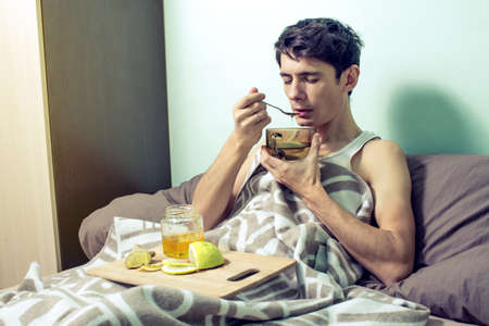 sickly: young man lies in bed sick with colds and the flu, head feels pain and suffering and treated in folk medicine, ginger, lemon, honey
