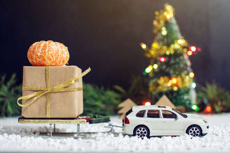 Toy car carries a gift for Christmas and New Year in the snow, on a black background.