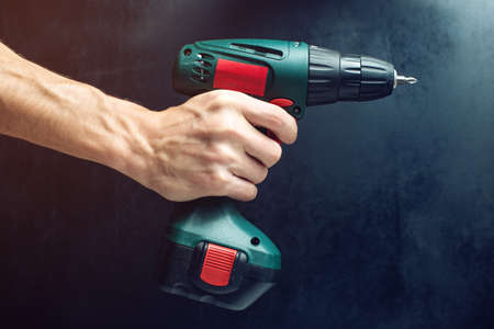 screwing: male hand holding a screwdriver, for screwing screws on black background