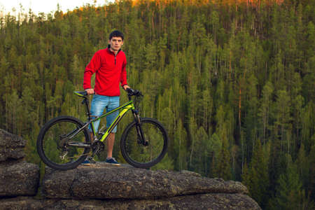 Cyclist with the mountain bike, the forest in the background Stock Photo