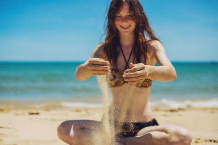 Sand as the time slips through your fingers. Girl holding a sand sea background
