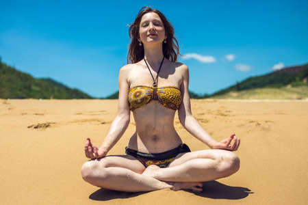 25 30 years: Portrait of a young woman meditating on beach