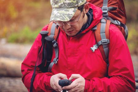 handheld device: tourist looking at the navigator in his hand standing on the path in the autumn forest Stock Photo