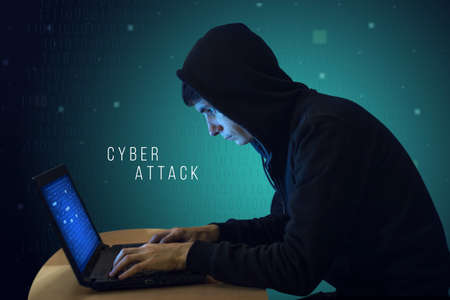 initiating: Hacker with laptop initiating the hacker attack, cyber war