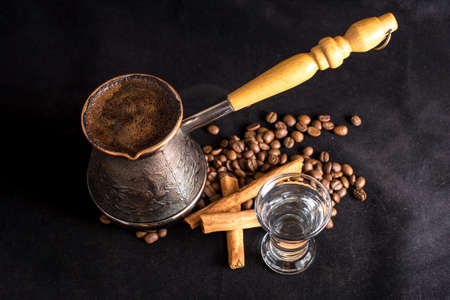 Turkish coffee, with coffee beans and cinnamon on dark background