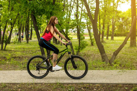 Happy girl cyclist riding on a mountain bike outside on the park. Adventure travel. lifestyle sport concept Banque d'images