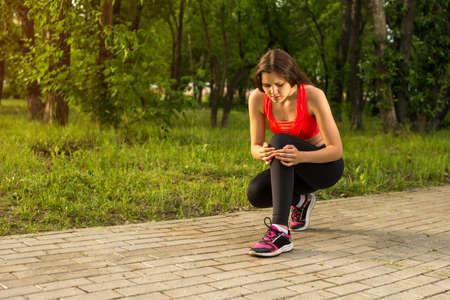 seizures: Woman in pain while running in park, knee injury, seizures Stock Photo