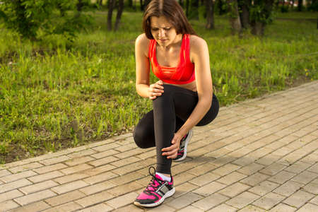 unrecognizable: Woman in pain while running in park, knee injury, seizures Stock Photo