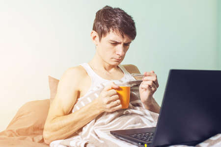 handkerchief: young man sick with a cold lying in bed, unwell with a thermometer wrapped in a blanket and working on the laptop