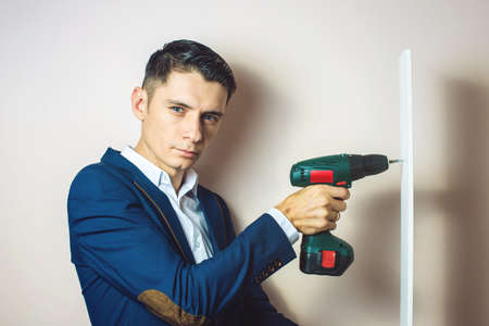 accumulator: man in suit twists the screwdriver a screw. businessman for dirty work Stock Photo