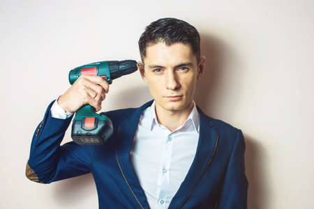 screwing: man in suit holding a screwdriver like a weapon, for screwing screws. businessman for dirty work