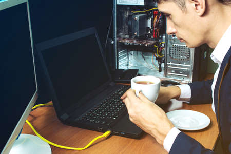 diagnoses: man in suit working with laptop diagnoses the failure of the computer and trying to fix it