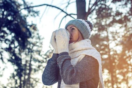 atraktivní žena v zimě, pletený svetr, rukavice a šátek, procházky parkem mezi stromy a sníh v lese pít horký čaj na pozadí slunečního světla