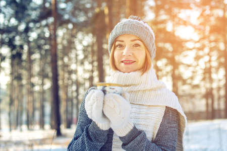 attractive woman in winter, a knitted sweater, mittens and scarf, walking through the Park among the trees and snow in the woods drinking hot tea on a background of sunlight