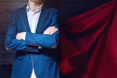 Superman. businessman standing in a suit and red cloak like a superhero on a dark background. the concept of progress in your career