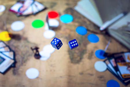 hand throws the dice on the background blurred colorful fantasy world map Board games, gaming moments in dynamics