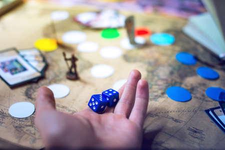 La mano lanza los dados en el fondo borrosa colorido mapa del mundo de fantasía Juegos de mesa, los momentos de juego en dinámica Foto de archivo - 70148122