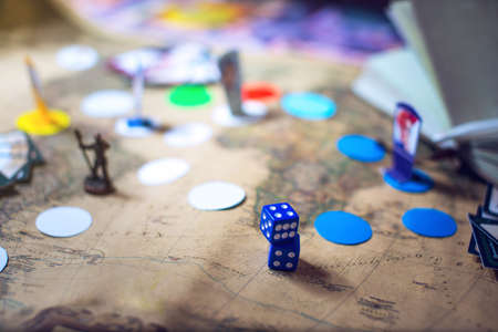 Dice are on the background blurred colorful fantasy Board games in the world map. moments in gaming dynamics Stock Photo