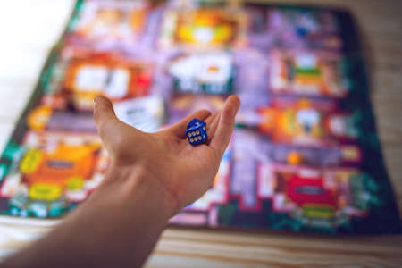 backgammon: Hand throws the dice on the background of colorful blurred fantasy Board games, gaming moments in dynamics Stock Photo
