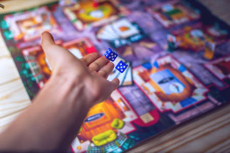 Hand throws the dice on the background of colorful blurred fantasy Board games, gaming moments in dynamics Stockfoto
