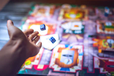 Hand throws the dice on the background of colorful blurred fantasy Board games, gaming moments in dynamics Banque d'images